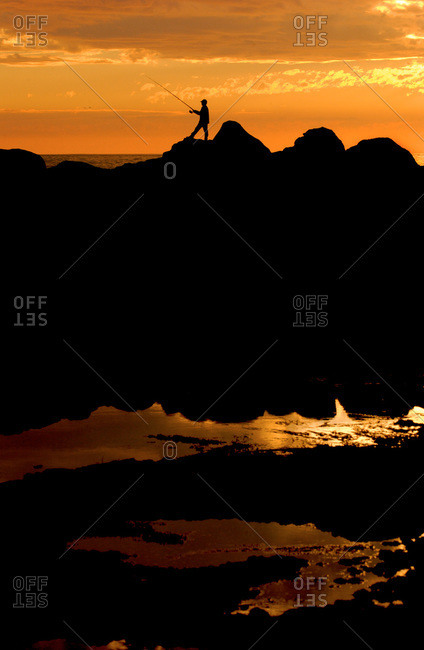 Silhouette of a man fishing at sunset in Ensenada, Mexico