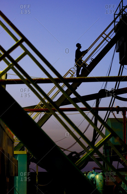 Silhouette of a man climbing up a drilling rig outside of Cairo, Egypt