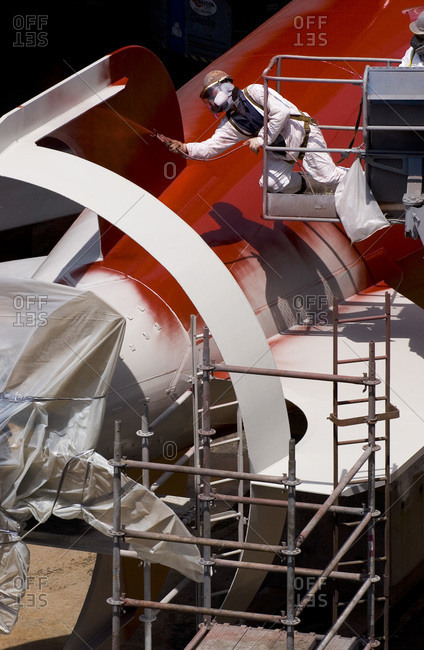 Worker painting the hull below the waterline of a vessel in dry dock in San Francisco, USA