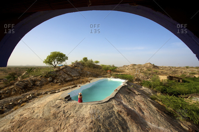 Woman sitting by a pool in Rajasthan, India