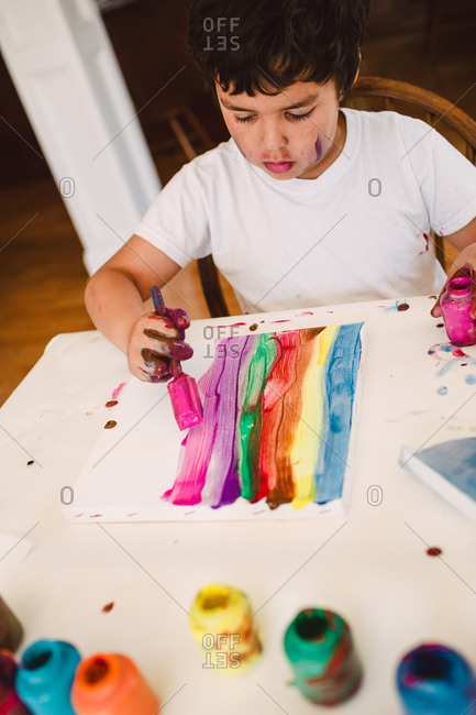 Boy painting colored stripes