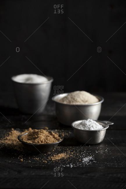 Four metal bowls filled with baking ingredients
