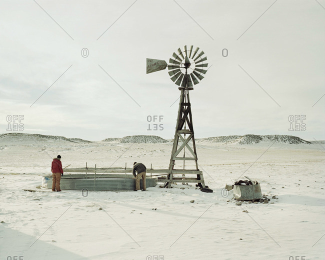 Breaking the ice in a frozen water tank next to a windmill