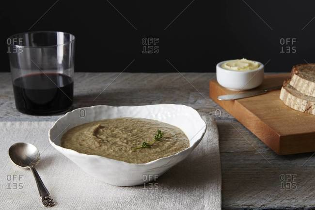 A bowl of mushroom soup sitting beside a soup spoon and a tumbler of wine