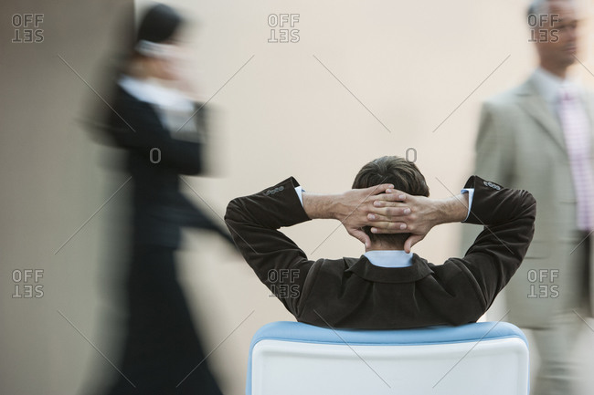 Businessman relaxing in busy lobby