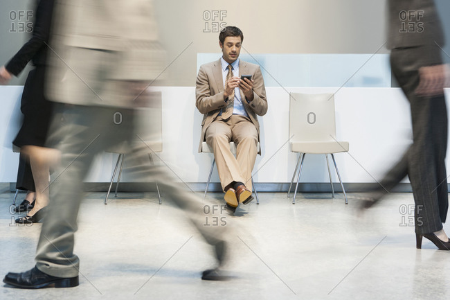 Businessman using cell phone in busy lobby area