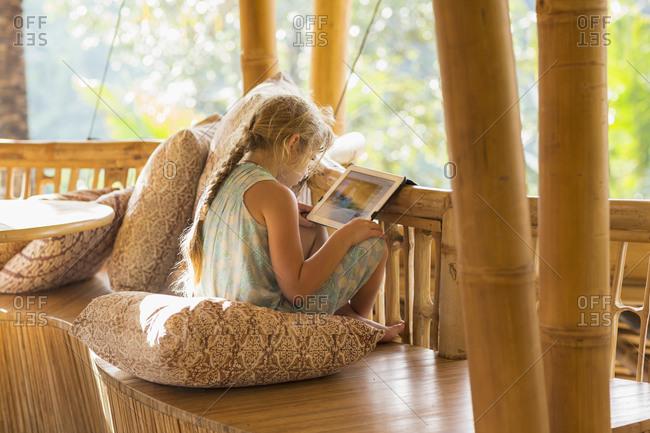 Girl using digital tablet on patio