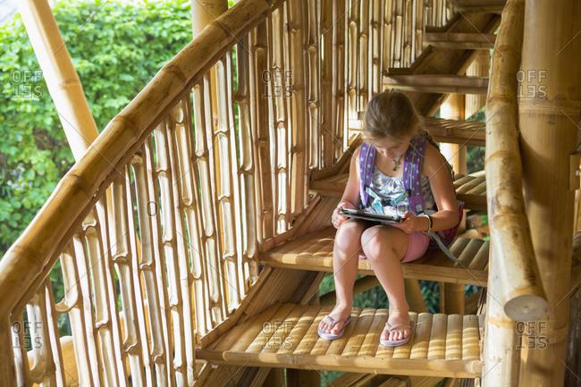 Caucasian girl reading on steps