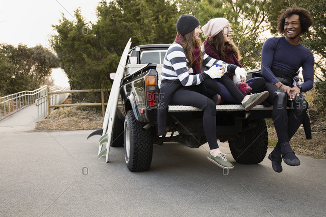 Friends having coffee together in truck bed