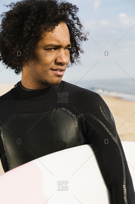 Mixed race surfer carrying board on beach