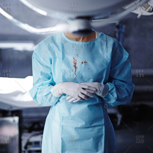 Caucasian surgeon with blood on gown in operating room
