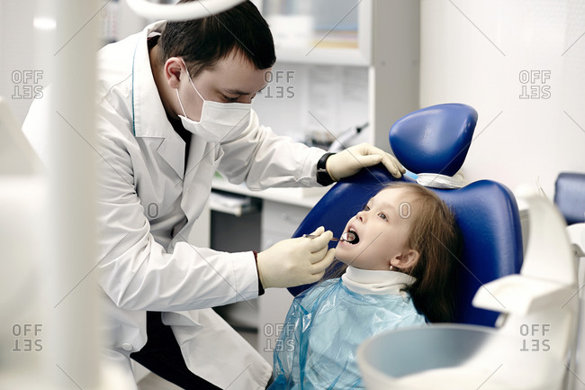 Caucasian dentist examining girl\'s teeth