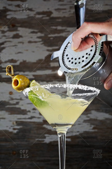 Pouring cocktail into martini glass rimmed with salt