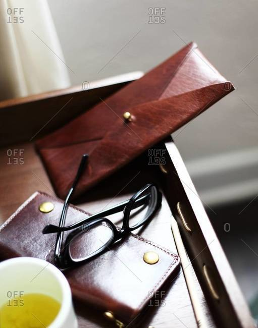 Still life of glasses, wallet and chamomile tea on tray
