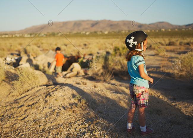 Children standing on a field in a bike helmet