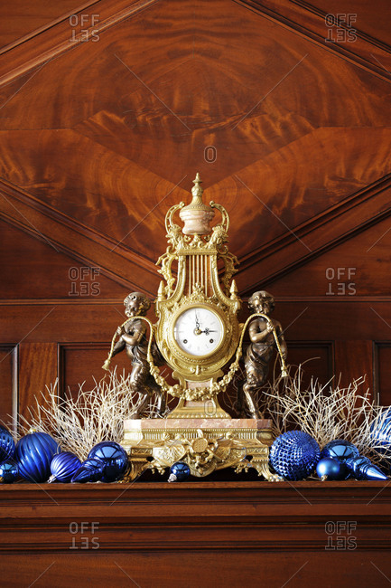 Mantle clock surrounded by ornaments