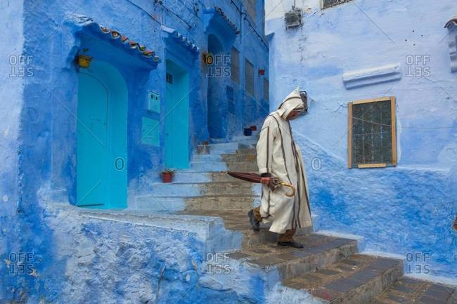 A man walks to work on a rainy morning in Chefchaouen, Morocco