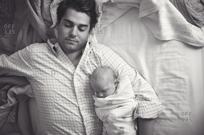 Tired man holds baby on bed