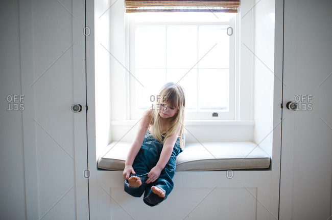 Young girl tries on adult jeans sitting by a window