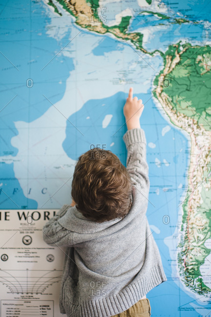 Young boy stretches to point to a place on a large map