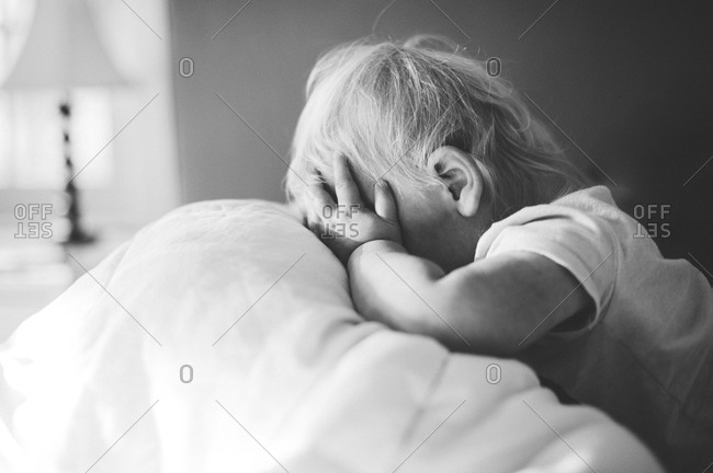 Baby covers face with hands in bed