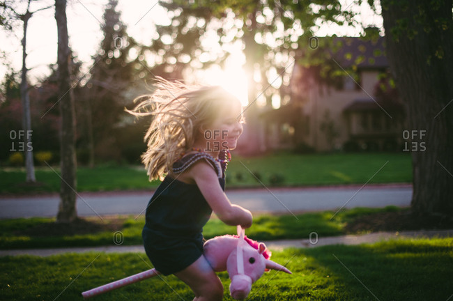 Girl rides toy unicorn outside as the sun sets
