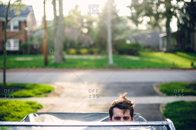 Man sits in convertible with messy hair
