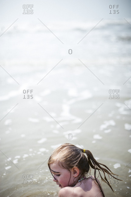 Young girl plays in surf at the beach