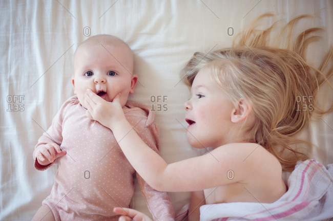 Young sister squeezes baby sister's cheek in bed