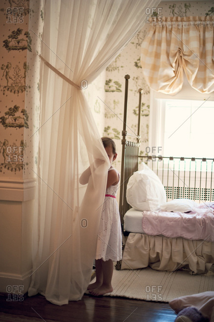 Young girl hides behind a curtain in her bedroom