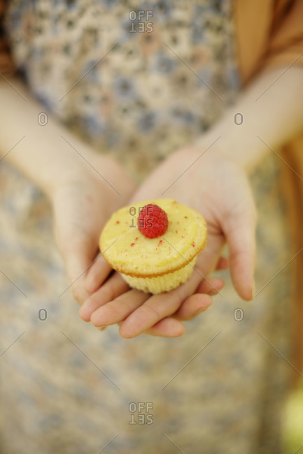 Woman offering a lemon cream cupcake