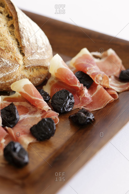 Slices of prosciutto with prunes on a cutting board