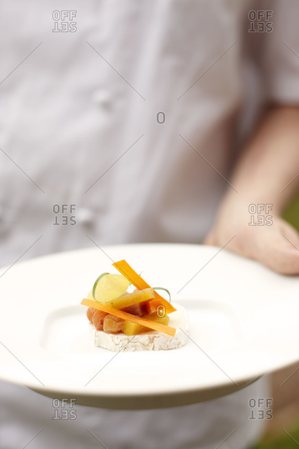 Chef holding appetizer on plate