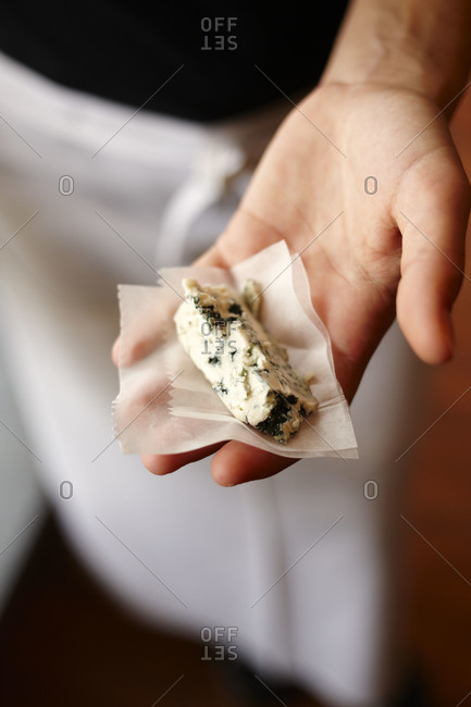 Man in apron holding a piece of blue cheese