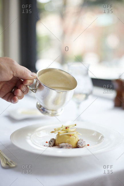 Person pouring celery root bisque over maple custard