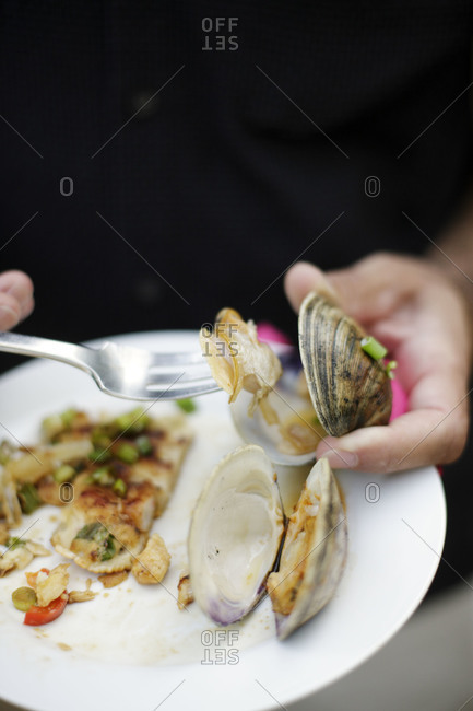 Close up of person eating clams