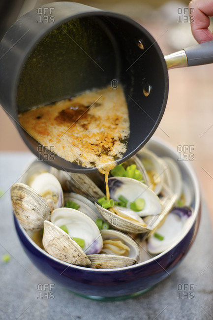 Person pouring sauce over clams