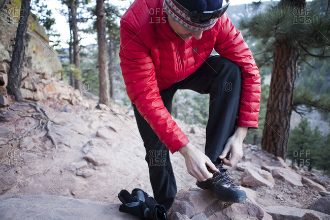 Man tying his shoelaces at a hiking trail