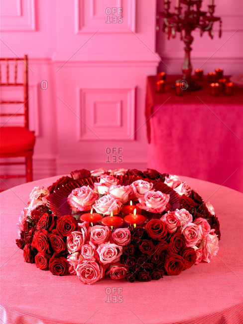 Red and pink roses on a table with candles