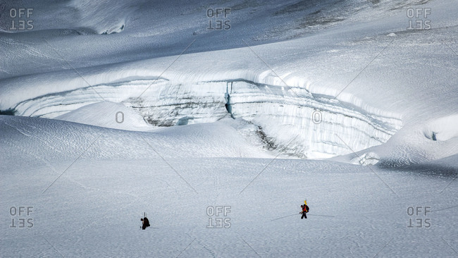 Two climbers roped together walking next to a gaping crevasse
