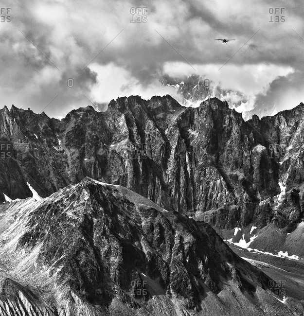 A bush plane flies away above the Ramparts and the Kahiltna glacier, Alaska Range