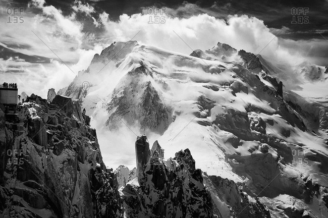 A climber finishes the Arete des Cosmiques on the Aiguille du Midi cablecar station, with the north face of Mont Blanc du Tacul in the background, Chamonix, France