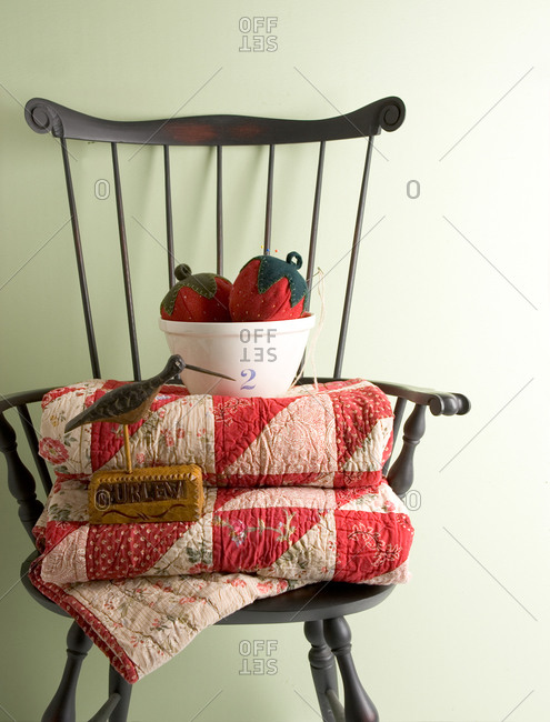 A vintage Windsor chair with folded quilts