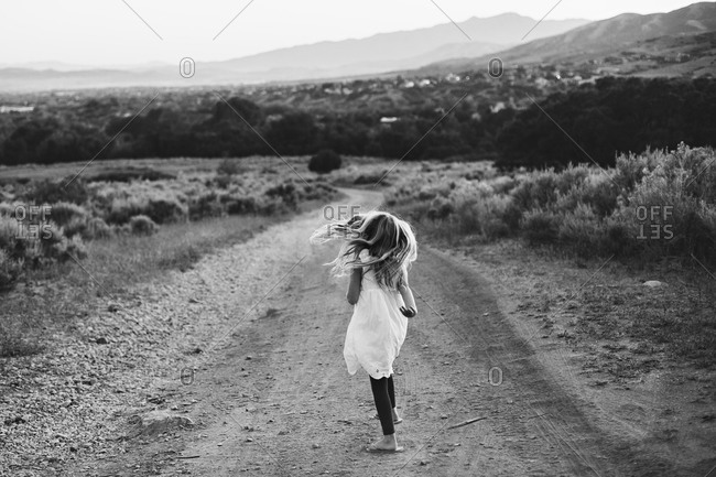 Young girl walking in on a dirt road in the countryside