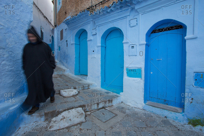 A man walks the narrow streets of Chefchaouen, Morocco