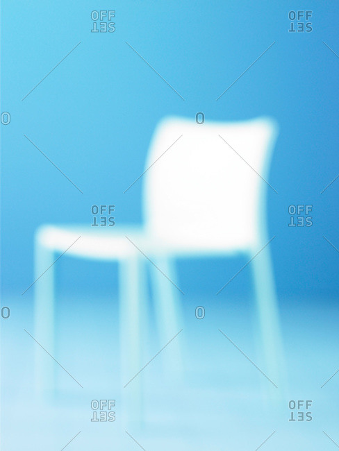 One white chair against a pale blue background