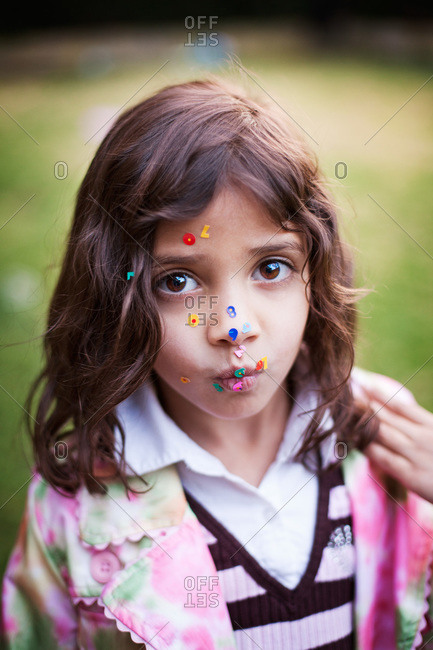 Portrait of a young girl with colorful sequins on her face