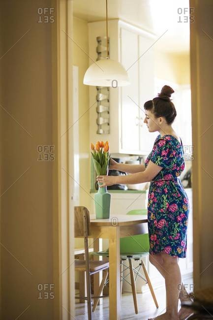 Side view of woman arranging tulips in vase