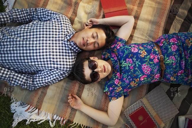 Couple lying head to head on picnic blanket