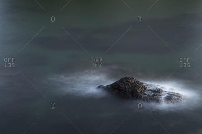 Waves hitting a rock outcropping island as seen from Salt Creek Recreation Area near Port Angeles, Washington